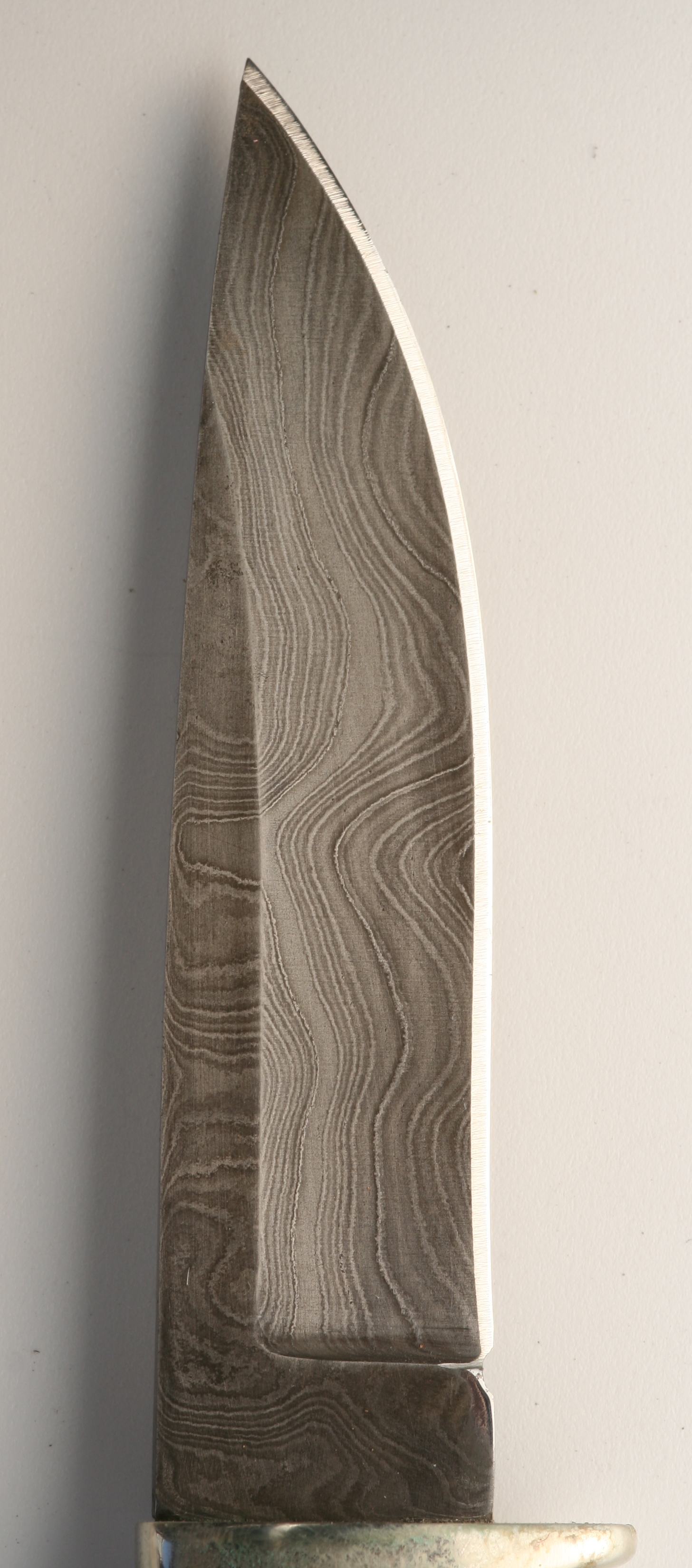 A damasus knife blade showing the folding or pattern welded appearance