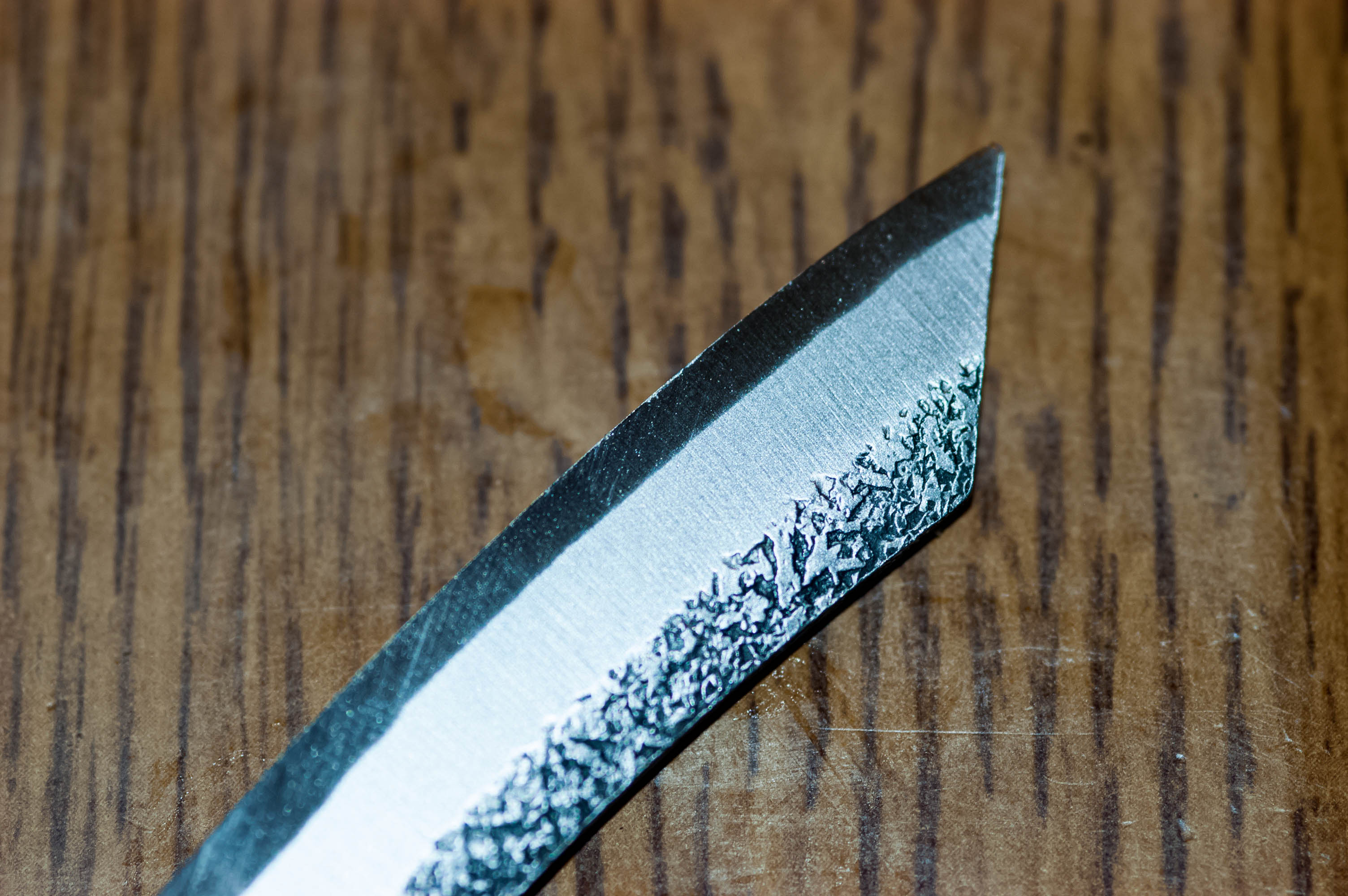 The knife blade itself, showing lamination and rough finish